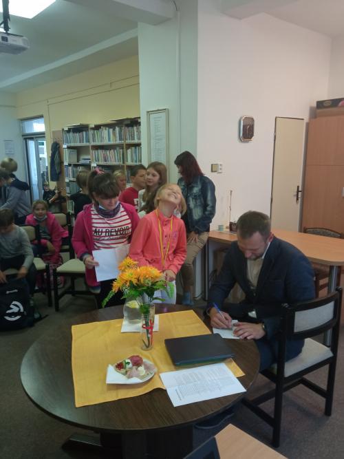 Spisovatel Michal Vlk v knihovně.